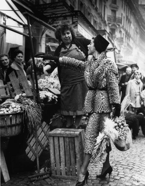 Marie Chantal en manteau d'Ocelot de Balmain, au marchŽ de la rue Mouffetard . Elle choisi ses lŽgumes en accord avec son panier. PubliŽ dans Life 1955 © Pierre Boulat / Cosmos