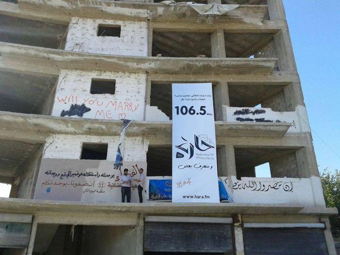 Affiche de Radio Hara sur un immeuble d'Alep, en Syrie. Photo : Radio Hara